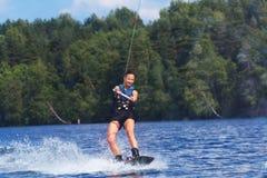 Νέα αρκετά λεπτή γυναίκα brunette που οδηγά wakeboard στο κύμα του mot Στοκ Φωτογραφία