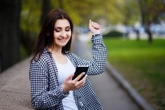 Νέα αρκετά μοντέρνη ενθουσιώδης γυναίκα που κρατά το έξυπνο τηλέφωνο στο s στοκ φωτογραφία με δικαίωμα ελεύθερης χρήσης