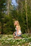 Νέα αρκετά ξανθή γυναίκα σε ένα λιβάδι με τα λουλούδια Στοκ Φωτογραφίες