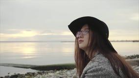 Νέα αρκετά wistful γυναίκα στο μαύρο καπέλο και γυαλιά που κάθονται κοντά στο ηλιοβασίλεμα θάλασσας απόθεμα βίντεο