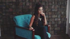 Νέα αρκετά wistful γυναίκα brunette που θέτει τη συνεδρίαση στην πολυθρόνα απόθεμα βίντεο