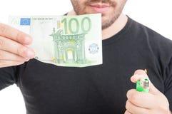Νέα αρσενικά καίγοντας χρήματα με τον αναπτήρα Στοκ Εικόνες