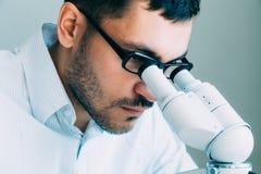 Νέα αρσενική εξέταση γιατρών μέσω του μικροσκοπίου Στοκ Φωτογραφίες