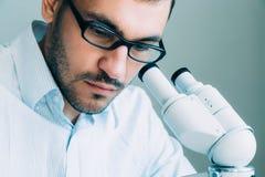 Νέα αρσενική εξέταση γιατρών μέσω του μικροσκοπίου Στοκ φωτογραφία με δικαίωμα ελεύθερης χρήσης
