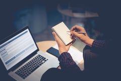 Νέα αρσενική εργασία με το σημειωματάριο και το σύγχρονο lap-top στη νύχτα Στοκ Εικόνες