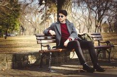 Νέα αρσενική συνεδρίαση hipster στο πάρκο Στοκ εικόνες με δικαίωμα ελεύθερης χρήσης