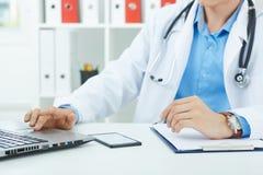 Νέα αρσενική συνεδρίαση γιατρών ιατρικής στον πίνακα και εργασία στο lap-top Στοκ εικόνες με δικαίωμα ελεύθερης χρήσης