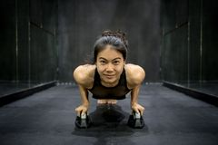 Νέα ασιατική γυναίκα αθλητών που κάνει την ώθηση επάνω στο πάτωμα Στοκ Φωτογραφίες