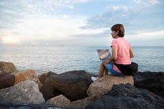 Νέα ασιατική γυναίκα ανεξάρτητη στη ρόδινη συνεδρίαση πουκάμισων στο βράχο στοκ φωτογραφίες