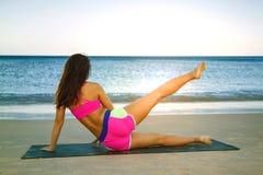 Νέα ασιατική γυναίκα ικανότητας στην παραλία που κάνει τις ασκήσεις πυρήνων στοκ φωτογραφία