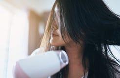 Νέα ασιατική γυναίκα μετά από το λουτρό που η τρίχα της με τη χτένα, θηλυκό που ξεραίνει την μακρυμάλλη με το στεγνωτήρα Στοκ Εικόνες