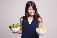Νέα ασιατική γυναίκα με τα τσιπ πατατών και τη σαλάτα Στοκ εικόνες με δικαίωμα ελεύθερης χρήσης