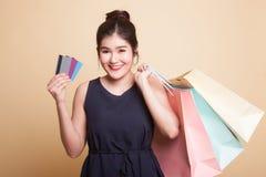 Νέα ασιατική γυναίκα με την τσάντα αγορών και την κενή κάρτα Στοκ Εικόνα