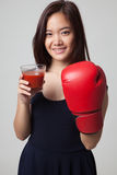 Νέα ασιατική γυναίκα με το χυμό ντοματών και το εγκιβωτίζοντας γάντι Στοκ εικόνα με δικαίωμα ελεύθερης χρήσης