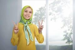 Νέα ασιατική γυναίκα μουσουλμάνος που δίνει το σημάδι ειρήνης Στοκ Εικόνες