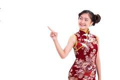 Νέα ασιατική γυναίκα ομορφιάς που φορά cheongsam και που δείχνει εκτός από το γ Στοκ Φωτογραφία