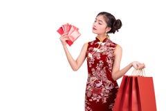 Νέα ασιατική γυναίκα ομορφιάς που φορά cheongsam και που κρατά τα χρήματα όπως Στοκ φωτογραφία με δικαίωμα ελεύθερης χρήσης