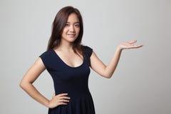 Νέα ασιατική γυναίκα παρούσα με το χέρι της Στοκ εικόνες με δικαίωμα ελεύθερης χρήσης