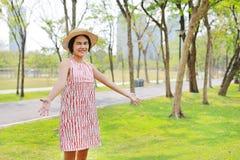 Νέα ασιατική γυναίκα που αυξάνει τα όπλα και το χαμόγελο στο πάρκο φύσης στοκ εικόνες