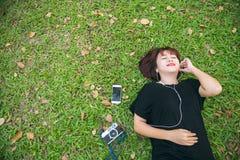 Νέα ασιατική γυναίκα που βάζει στην πράσινη χλόη που ακούει τη μουσική στο πάρκο με μια ψυχρή συγκίνηση Στοκ φωτογραφίες με δικαίωμα ελεύθερης χρήσης