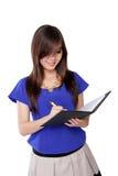 Νέα ασιατική γυναίκα που γράφει στο σημειωματάριο, που απομονώνεται στο λευκό Στοκ Εικόνα