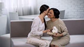 Νέα ασιατική γυναίκα που κάνει το δώρο στον ώριμο θηλυκό φίλο, που γιορτάζει την επέτειο στοκ φωτογραφία με δικαίωμα ελεύθερης χρήσης