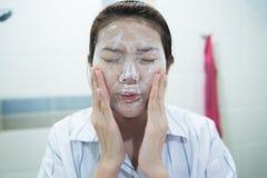 Νέα ασιατική γυναίκα που καθαρίζει το πρόσωπό της με τον του προσώπου αφρό στο λουτρό Στοκ Εικόνες