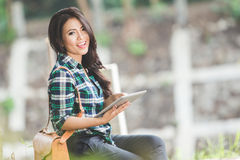 Νέα ασιατική γυναίκα που κρατά ένα PC ταμπλετών καθμένος στο πάρκο Στοκ εικόνες με δικαίωμα ελεύθερης χρήσης