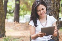 Νέα ασιατική γυναίκα που κρατά ένα PC ταμπλετών καθμένος στο πάρκο Στοκ φωτογραφία με δικαίωμα ελεύθερης χρήσης