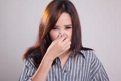 Νέα ασιατική γυναίκα που κρατά τη μύτη της λόγω μιας κακής μυρωδιάς Στοκ Εικόνες