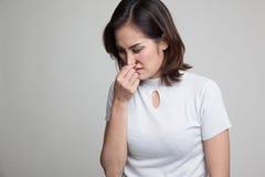 Νέα ασιατική γυναίκα που κρατά τη μύτη της λόγω μιας κακής μυρωδιάς στοκ φωτογραφία