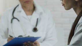 Νέα ασιατική γυναίκα που λέει τα συμπτώματα, γιατρός που ακούνε και που κρατούν τις ιατρικές αναφορές απόθεμα βίντεο