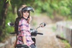 Νέα ασιατική γυναίκα που οδηγά μια μοτοσικλέτα σε ένα πάρκο Στοκ Εικόνα