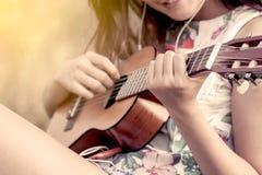 Νέα ασιατική γυναίκα που παίζει το ακουστικό guitalele Στοκ φωτογραφίες με δικαίωμα ελεύθερης χρήσης