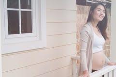 Νέα ασιατική γυναίκα που στέκεται στο μπαλκόνι που χαμογελά με την ευχαρίστηση μπαζούκας Στοκ φωτογραφία με δικαίωμα ελεύθερης χρήσης