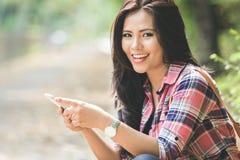 Νέα ασιατική γυναίκα που χρησιμοποιεί ένα κινητό τηλέφωνο καθμένος στο πάρκο Στοκ φωτογραφία με δικαίωμα ελεύθερης χρήσης