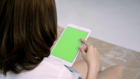 Νέα ασιατική γυναίκα που χρησιμοποιεί τη μαύρη συσκευή ταμπλετών με την πράσινη οθόνη φιλμ μικρού μήκους