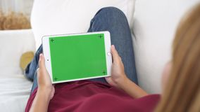 Νέα ασιατική γυναίκα που χρησιμοποιεί τη μαύρη συσκευή ταμπλετών με την πράσινη οθόνη απόθεμα βίντεο