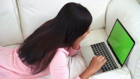 Νέα ασιατική γυναίκα που χρησιμοποιεί τη συσκευή lap-top με την πράσινη οθόνη απόθεμα βίντεο