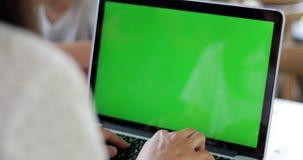 Νέα ασιατική γυναίκα που χρησιμοποιεί το φορητό προσωπικό υπολογιστή με την πράσινη οθόνη απόθεμα βίντεο