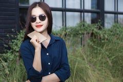 Νέα ασιατική γυναίκα στα ενδύματα casule που φορούν τα γυαλιά ηλίου που κρατούν το γ Στοκ Φωτογραφία