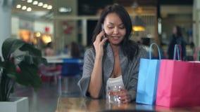 Νέα ασιατική γυναίκα στο τηλέφωνο μετά από να ψωνίσει στη λεωφόρο απόθεμα βίντεο