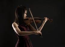 Νέα ασιατική γυναίκα playng το βιολί στο Μαύρο Στοκ φωτογραφία με δικαίωμα ελεύθερης χρήσης