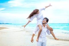 Νέα ασιατική εν πλω παραλία ερωτευμένου μήνα του μέλιτος ζευγών στο μπλε ουρανό σύζυγος που δίνει piggyback το γύρο στη σύζυγο ευ στοκ φωτογραφία με δικαίωμα ελεύθερης χρήσης
