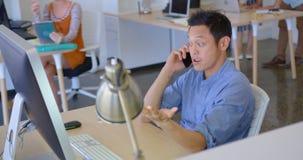 Νέα ασιατική επιχειρησιακή αρσενική εκτελεστική ομιλία στο κινητό τηλέφωνο στο σύγχρονο γραφείο 4k φιλμ μικρού μήκους