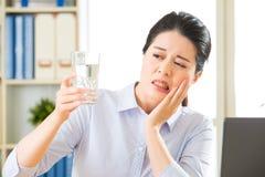 Νέα ασιατική επιχειρησιακή γυναίκα με ευαισθησία δοντιών Στοκ Εικόνες