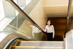 Νέα ασιατική θηλυκή εκτελεστική να ανεβεί κυλιόμενη σκάλα Στοκ φωτογραφίες με δικαίωμα ελεύθερης χρήσης