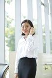 Νέα ασιατική θηλυκή εκτελεστική ομιλία στο τηλέφωνο Στοκ Φωτογραφία