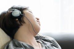 Νέα ασιατική μουσική ακούσματος τρίχας γυναικών σύντομη Στοκ Εικόνα
