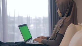 Νέα ασιατική μουσουλμανική γυναίκα που χρησιμοποιεί το lap-top με την πράσινη οθόνη στο σπίτι απόθεμα βίντεο